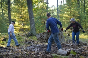 Two men and a woman clean up dumped trash and debris from state forest land in Grand Traverse County, Michigan