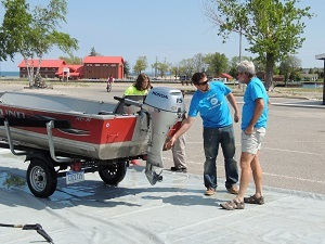A volunteer helps a boater remove plants and debris from a boat and trailer