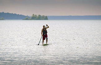 A man uses a paddle board on calm waters.