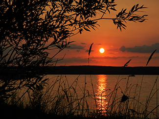 A beautiful orange-red sunset is shown from Burt Lake State Park.