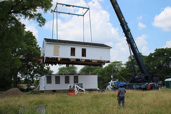 A crane lifts the second story of a home and prepares to set it down next to the first story.