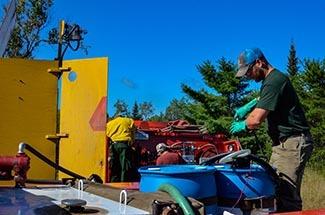 A work crew prepares a skidder for a herbicide treatment.