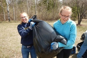 Two young women moving a black garbage bag, after cleaning up a dump site in a Michigan forest