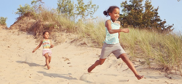 two little girls running single file along the beach