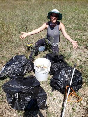 A person poses next to buckets and bags of trash cleaned from the forest