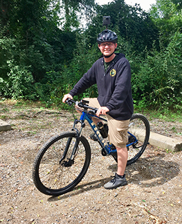 Brad Parsons, story author and DNR videographer, is shown sitting on his mountain bike.