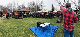 An organizer speaks to a large group of bikers at Sleepy Hollow State Park in Clinton County.