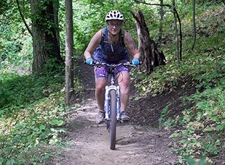 A mountain biker is shown on a flow trail.