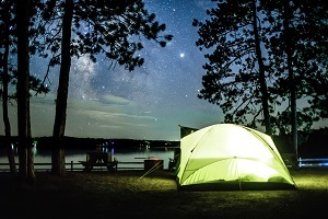 a yellow tent, glowing with inside light, nestled among shadowed trees next to water and a star-filled night sky