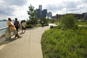 Visitors take in the sights along the Detroit Riverfront, the Renaissance Center in the background
