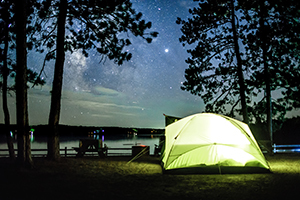 tent on wooded campsite by lake at night