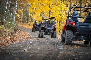 ORVs on wooded trail with fall foliage