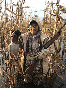 female waterfowl hunter in wetland holding duck