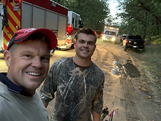 Michael and Brett Postema pictured with emergency vehicles Thursday.