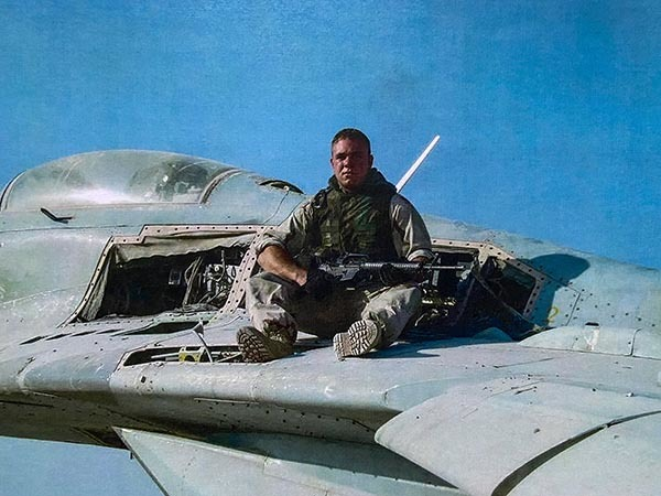 Conservation officer Chris Maher is shown on a military aircraft.