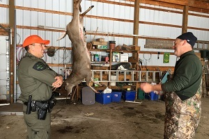 A DNR conservation officer talks with a male hunter, in a pole barn, with a harvested deer hanging in the background
