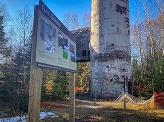 A sign interpreting the history of the stamp sands is show at the base of the smokestack from the Mohawk Mill.
