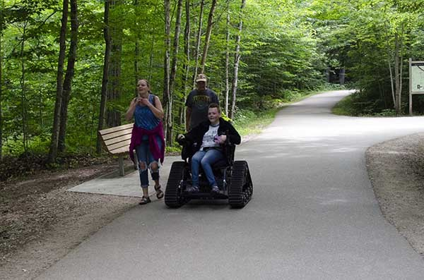 A visitor uses a track chair at Tahquamenon Falls State Park in Luce County.