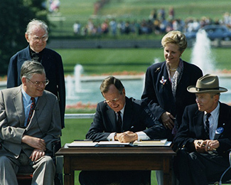 George H.W. Bush signs the Americans with Disabilities Act in July 1990.