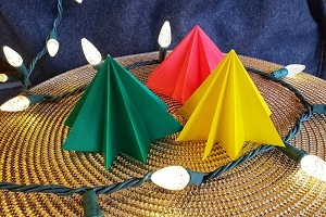 red, yellow and green origami pine tree-shaped trees, on a woven mat and surrounding by white holiday lights