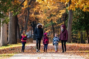 A family dressed in fall coats, walks toward the camera along a fall trail, forest in the background, autumn leaves on ground