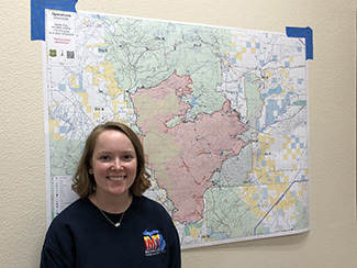 The DNR's Paige Gebhardt stands in front of a map she helped create on the Mullen Fire in Wyoming.