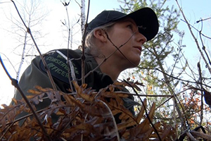 female conservation officer in woods, observing