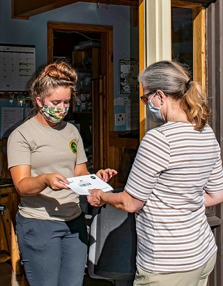 A masked, female DNR parks and recreation seasonal worker helps a woman with camping check-in