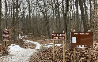 new signs showing open hours and Recreation Passport requirement at trail entrance in woods at Van Buren State Park