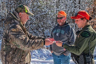 A conservation officer talks with two hunters on a November day.
