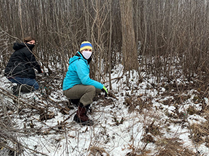 two female volunteers in face masks in snowy forest