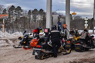 A group of snowmobilers gasses-up their machines at a service station in Ontonagon County.