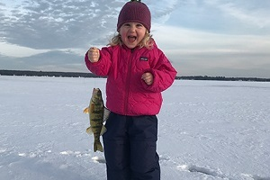 little girl ice fishing and holding up her catch
