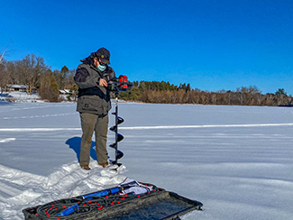 A DNR staffers uses an auger to drill a hole in the ice on an Upper Peninsula lake.