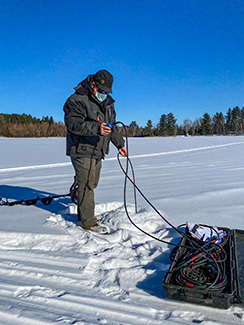 A DNR staffer is shown conducting a dissolved-oxygen test at an Upper Peninsula lake.
