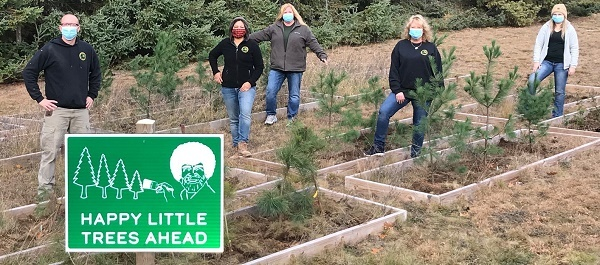 a small group of masked women and men stand with planted trees and a Happy Little Trees Ahead green sign at Higgins Lake State Park