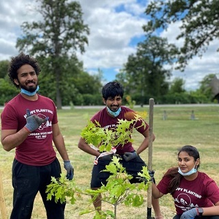 Two men and a woman wearing Happy Little T-shirts pose with a tree they are planting at Belle Isle in Detroit