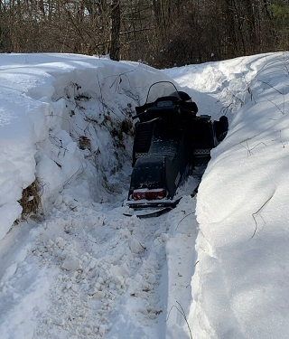 view of a snowmobile partially buried under snow on a trail in the forest