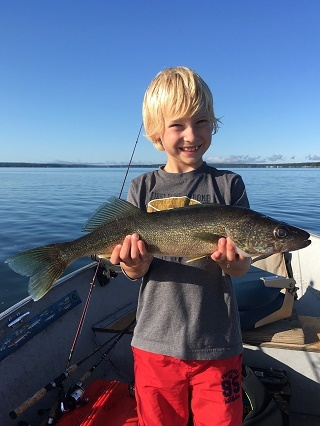 young, smiling blond boy holding a walleye in both hands, standing on a boat on a Michigan inland lake