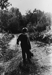 Historical photo of boy walking on trail carrying a fishing pole