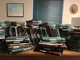 Logbooks from the cabins and yurts at Porcupine Mountains Wilderness State Park are shown stacked.