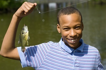 young boy smiling and holding up a fish on a line