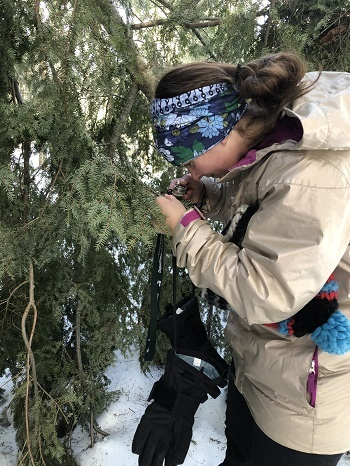 a woman wearing a tan coat and floral headband uses a hand lens to inspect a tree in the forest