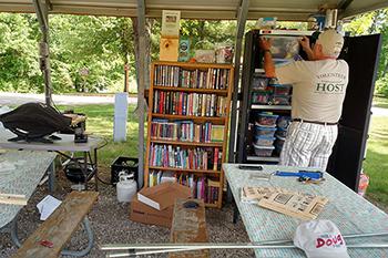 volunteer campground host removes activity bin from shelf