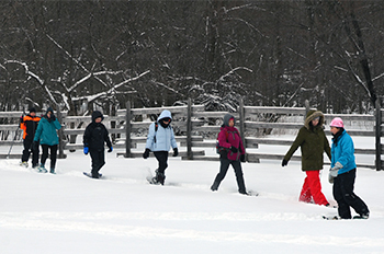 A Becoming an Outdoorswoman snowshoeing class enjoying an afternoon during a February gathering.