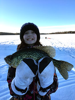 Jennifer Johnson's daughter, Rhiannon, proudly holds up the crappie she caught in Dickinson County.