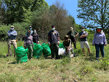group of volunteers in face masks with garbage bags