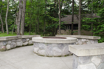 brick patio with fire pit and benches with lodge and woods in background