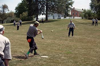 A base ball game at the Walker Tavern played during modern times with players dressed in 1920's-era uniforms.