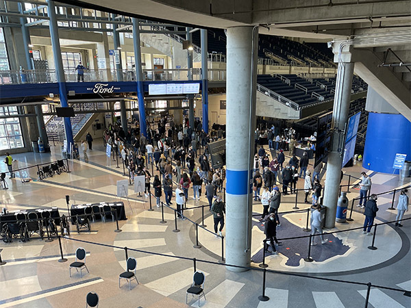 A line is shown at Ford Field of people waiting for their chance to be vaccinated.
